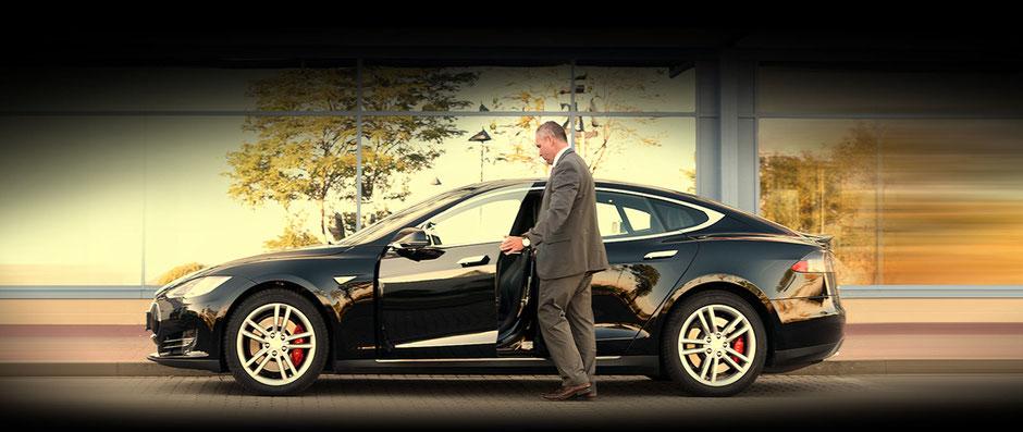 Mann im Anzug, der gerade vor einer verglasten Häuserfront, in der sich Bäume spiegeln, in einen schwarzen Tesla einsteigt