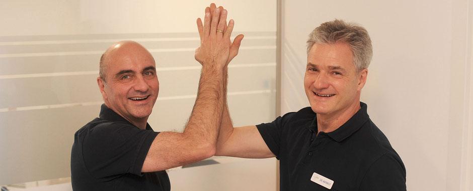 Die Zahnärzte Dr. Uwe Maiwald und Dr. Jens Staudenmayer aus Ludwigsburg geben sich lächelnd ein High Five in der Gemeinschaftspraxis Maiwald Staudenmayer