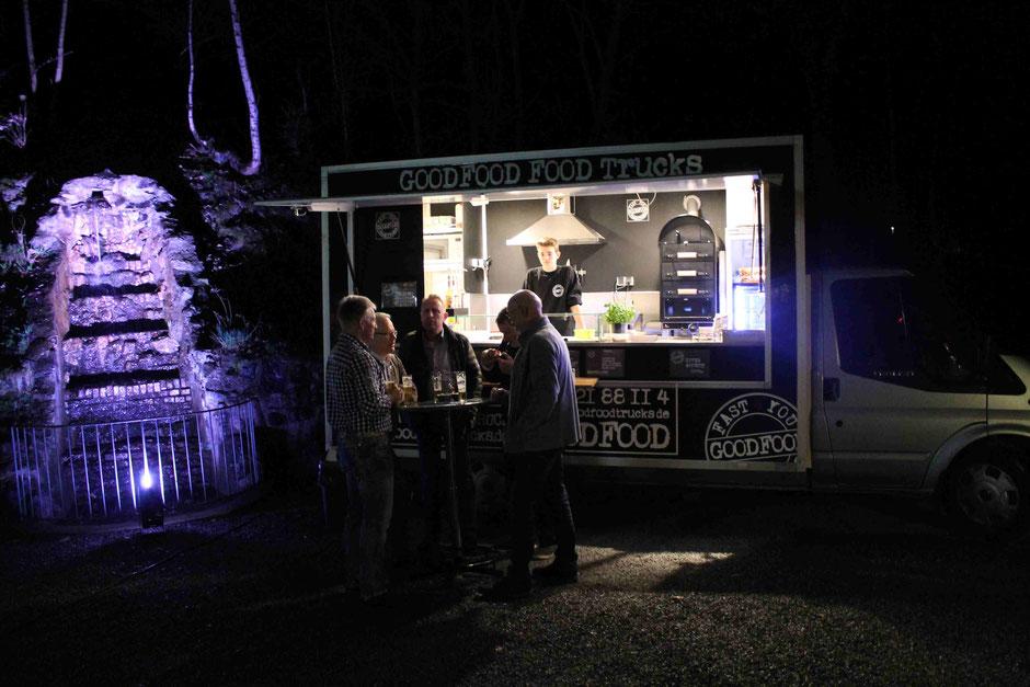 Gruppe am Stehtisch vor dem GOODFOOD FOOD TRUCK, Nachtaufnahme mit beleuchtetem Brunnen im Hintergrund des Food Trucks