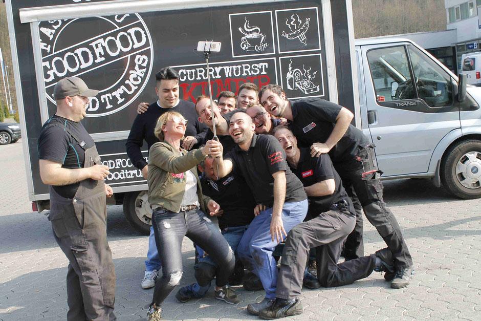 Selfie bild der Mitarbeiter Autofit Ludwig vor dem GODDFOOD FOOD TRUCK