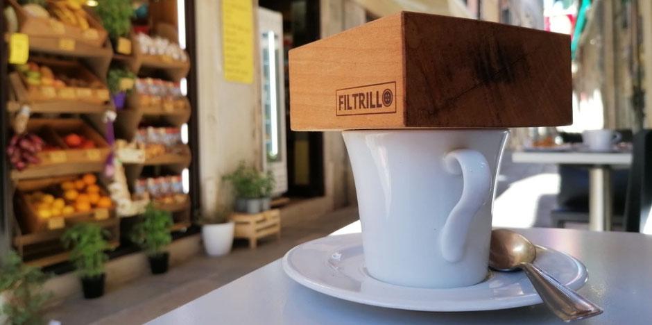 Kaffeefilter aus Holz auf weißer Tasse mit Löffel und Unterteller auf Tisch vor Gemüsehändler