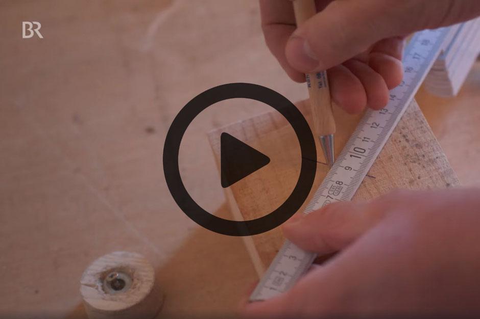 Hände zeichnen mit Kugelschreiber und Zollstock auf Holzklotz unter Videosymbol.