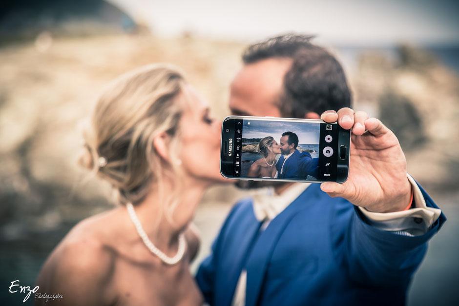 Jeunes mariés qui s'embrassent en selfie