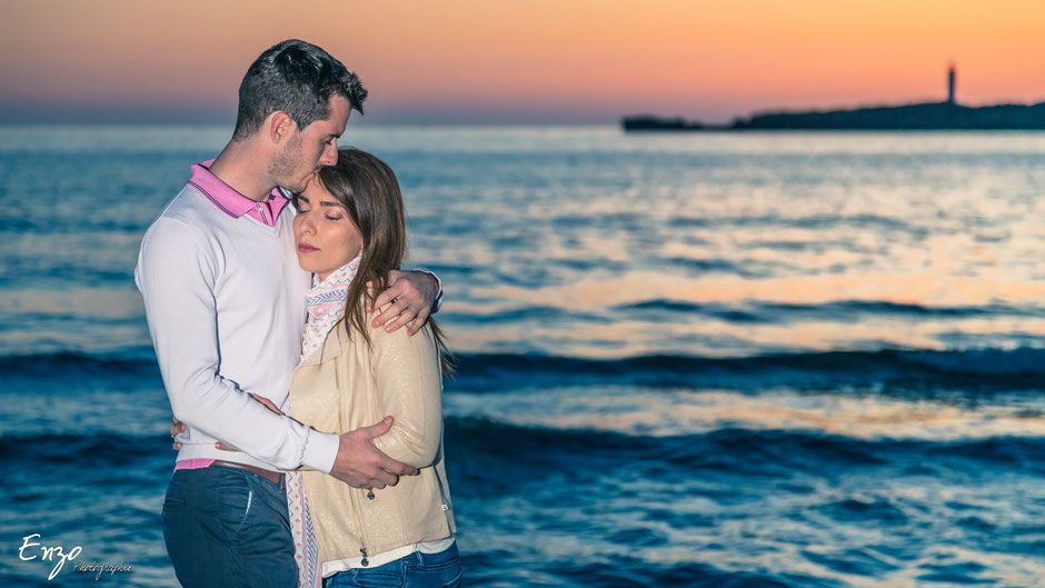 Jeune couple amoureux en bord de mer lors d'une séance de couple au coucher du soleil