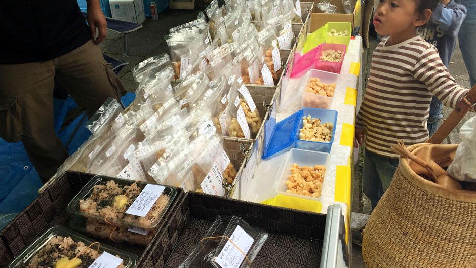 「Vege&Fork Market」(神奈川県川崎市麻生区)で出会った、あられ本舗おもやの、高橋重光さんです。たくさんの試食。お客さんに包囲され、接客で息つく暇もない。