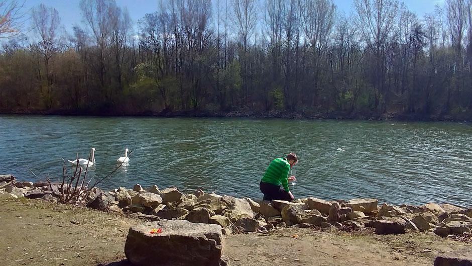 Mann knienend an eniem Kanalufer