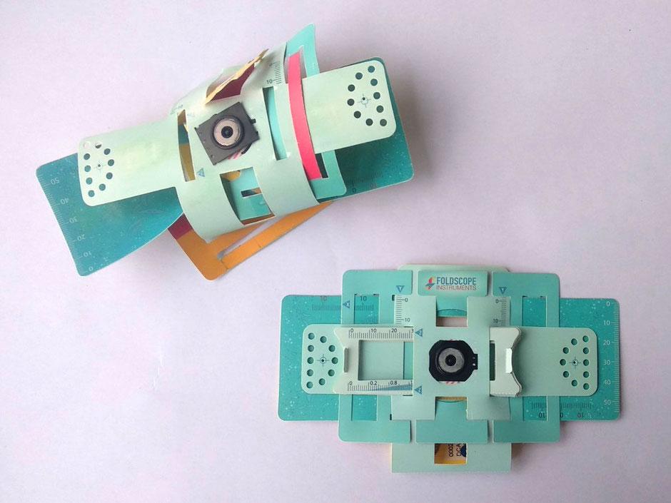 Zwei Foldscopes – das Foldscope oben links ist ganz offensichtlich falsch aufgebaut, das unten rechts ist korrekt aufgebaut.