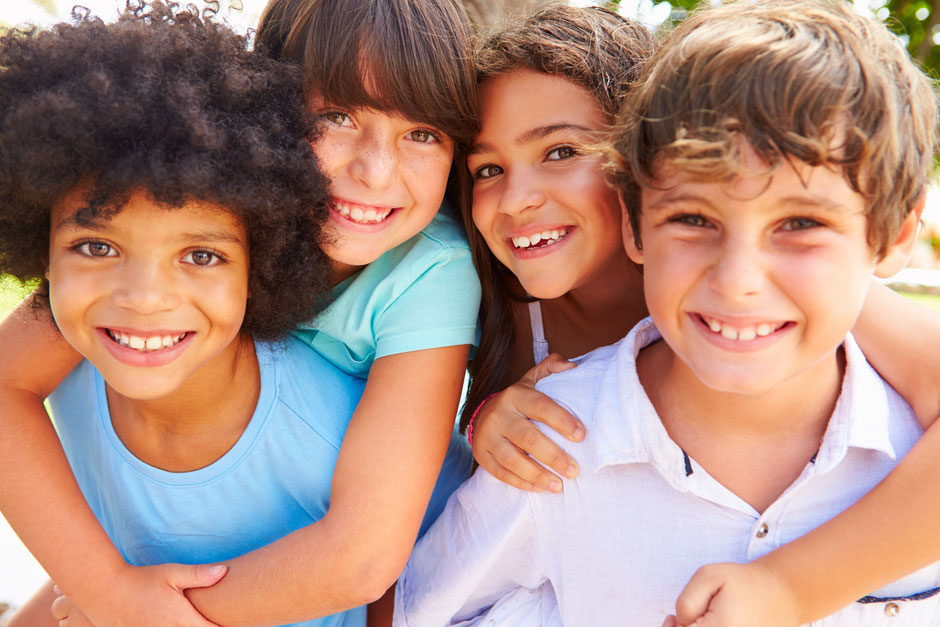 Kinder umarmen sich und präsentieren die Seite Kontakt von der Grundschule in Geldern