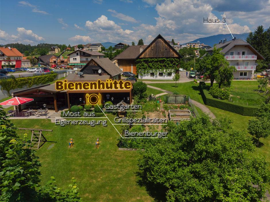 Bild vom Gastgarten und Gasthaus Bienenhütte mit Beschriftung sowie Ferienwohnungen Haus Nummer 3.