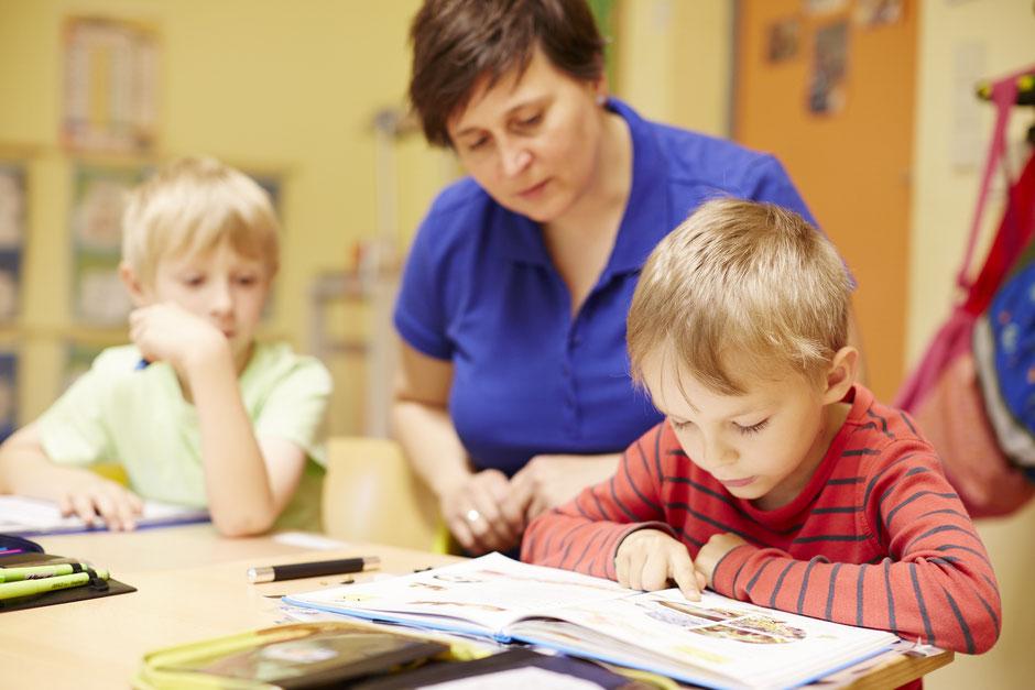 Foto: Hortleiterin Deborah Engler mit Kindern bei der Hausaufgabenhilfe