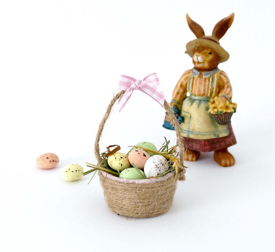 Minikorb mit kleinen farbigen Zuckereiern gefüllt