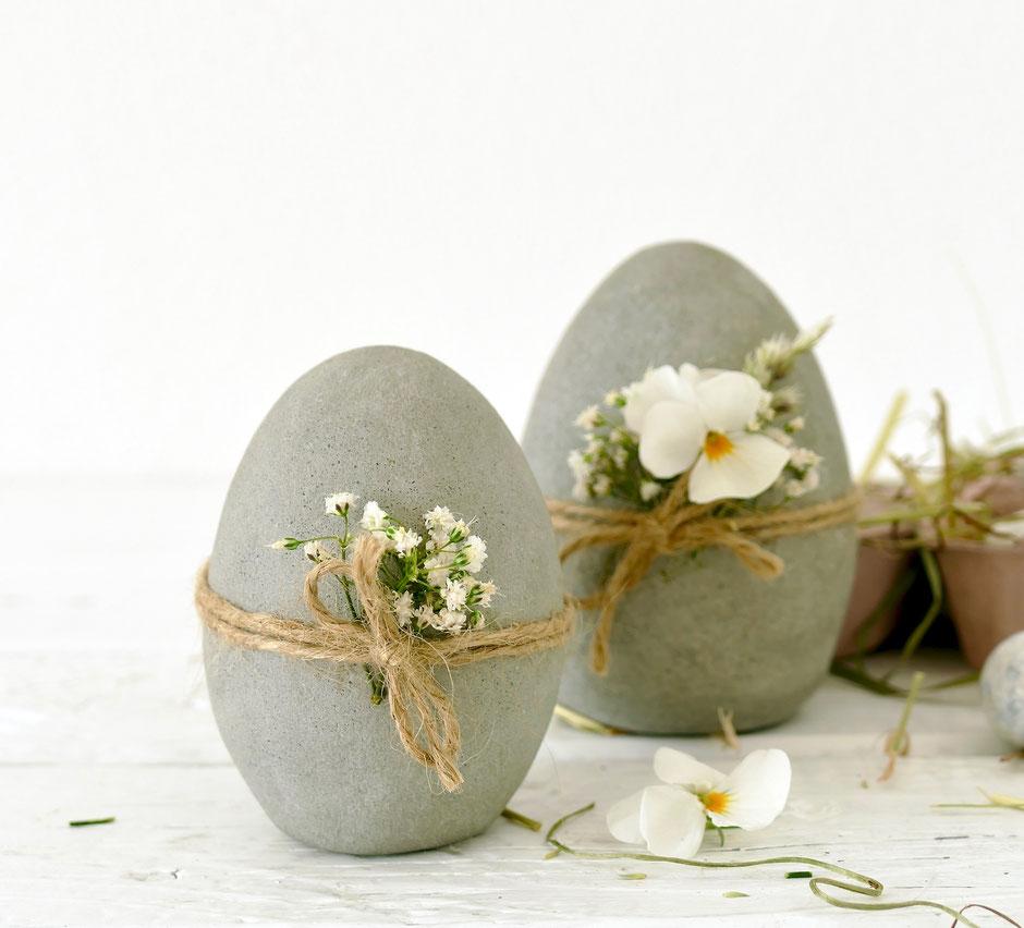 Selbst gemachte Ostereier aus Beton mit Schnur und Blüten verziert