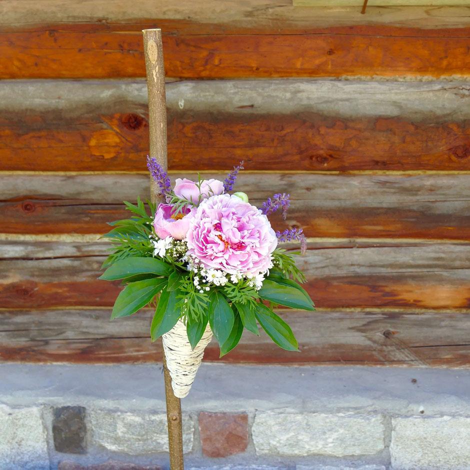 Sommerlicher rosa Blumenstrauss in einer weissen Spitztüte am Stock fest gemacht