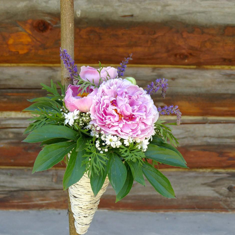 Bunter Blumenstrauss in einer Tüte an einen Stock gebunden