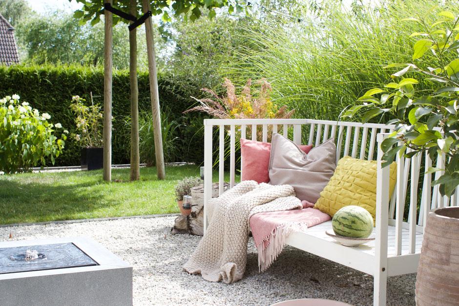 dieartigeBLOG - Gartenbank mit Kissen in Rosa und Zitronengelb, Kies-Terrasse, Gräser, Brunnen
