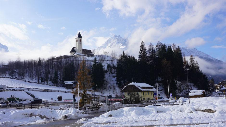 Der Kirchturm von Vierschach thront über dem Dorf und dem Schnee