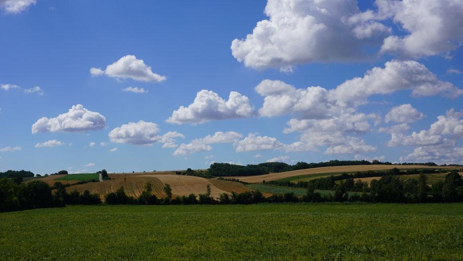 Wolkenspiel über hügeliger Landschaft