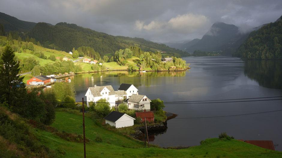 Sonnenspot auf ein paar Häuser am Fjord