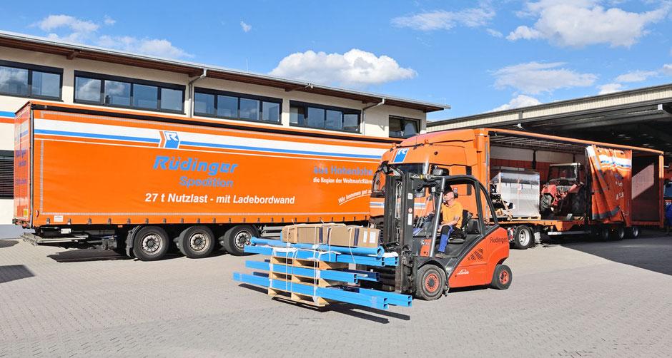 Man sieht eine Aneinanderstellung gewaltiger Maschinentransport LKW in ornage. Es hat blauen Himmel mit weißen Wolken, die Trucks sind orange. Im Himmel steh Transport Überlänge Rüdinger Spedition.