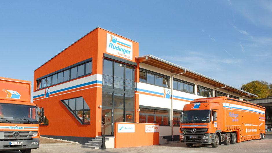 Maschinentransport aus Leidenschaft steht oben links in großen Lettern. Vor einem orangenem modernen Neubau steht ein riesiger LKW für Maschinentransporte in oragnener Farbe. Links sieht man einen kle