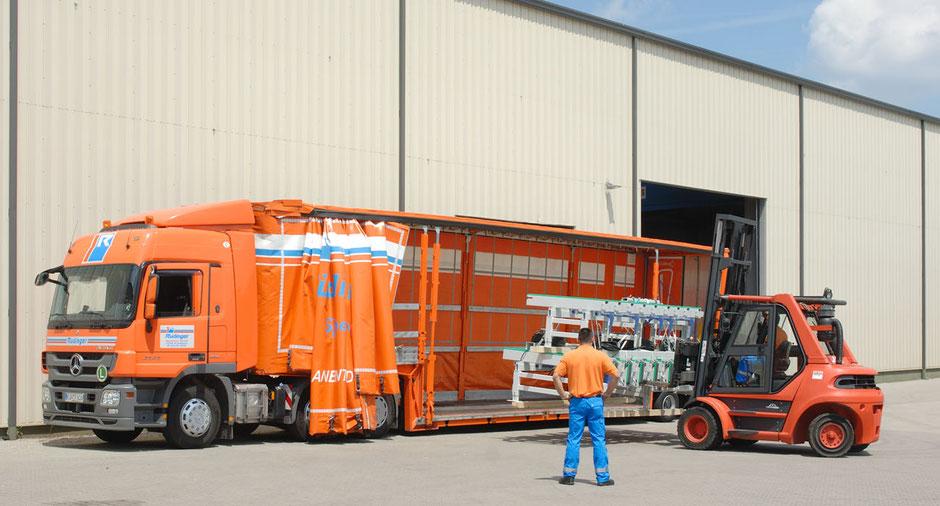 Im Bild sieht man auch die Worte Maschinentransporte aus Leidenschaft. Vor einer Halle steht ein gewaltiger Maschinentransport LKW. Ein Stapler navigiert eine Maschine auf die Ladefläche.