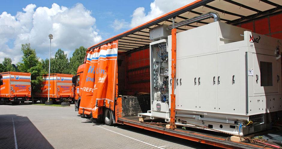 Man sieht einen Maschinentransport LKW mit 3 grünen landwirtschaftlichen Maschinen. an der Seite ist die Plane offen. Der Maschinentransporter ist orange, er steht auf dem Betriebshof.