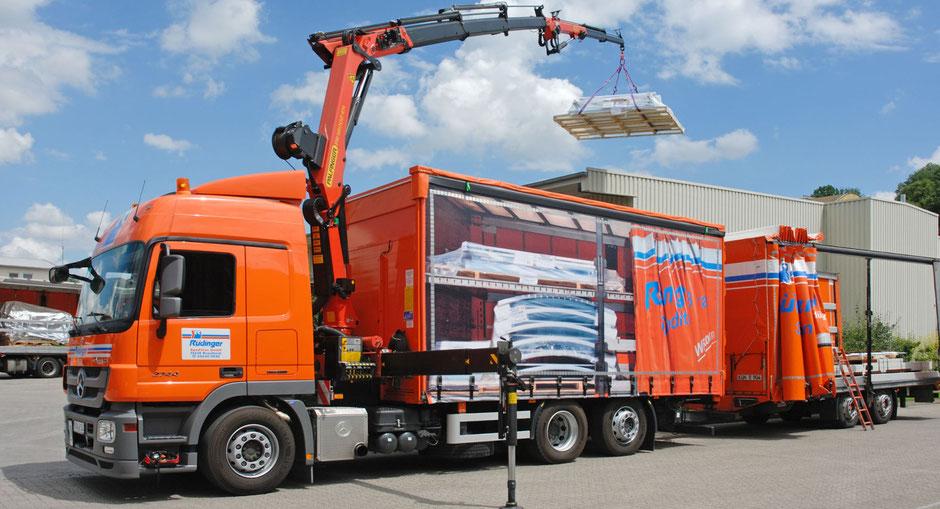 Neben der Maschinenlogistik bietet die Rüdinger Spedition auch Baustellen Logistik, das steht auch im Himmel. Ein großer LKW mit Hänger steht vor einer Baustelle, ein Mann im Stapler ist davor.