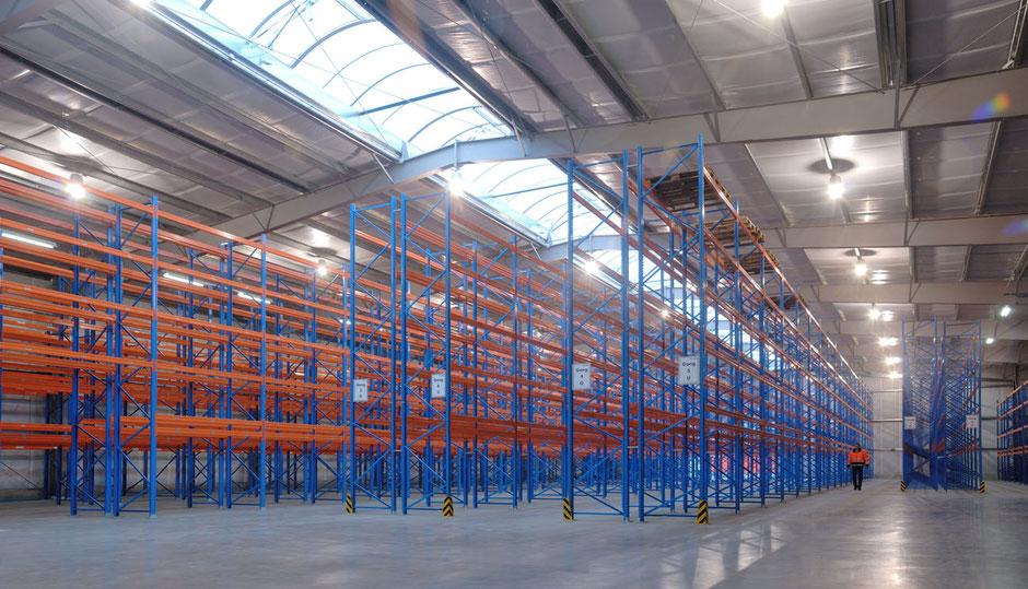 Man sieht das leere Lager einer Spedition. Die Ausmasse sind gewaltig. Im Bild steht oben 20.000 Quadratmeter Lagerfläche Rüdinger Spedition.