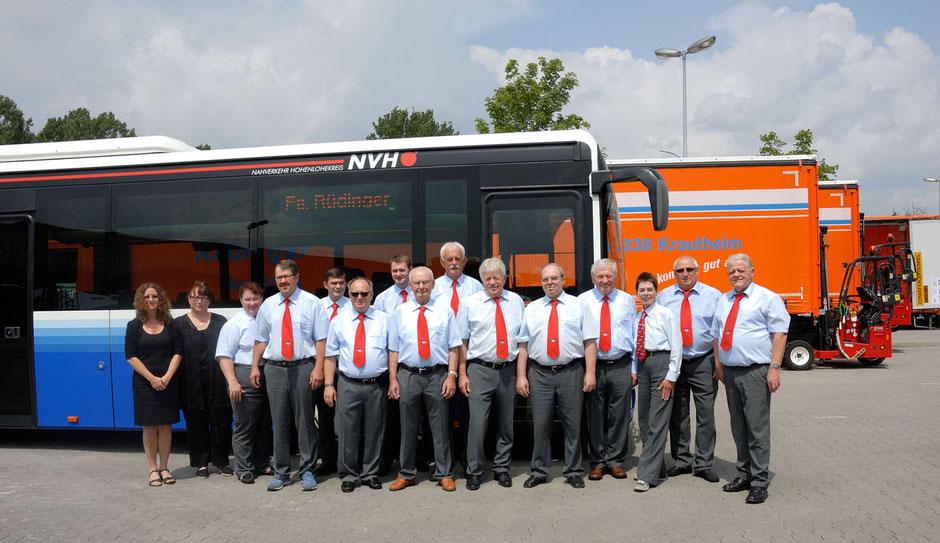 Vor verschiedenen LKW für Maschinentransporte ist ein blauer Bus für ein Gruppenfoto bereit gestellt. Davor sind 13 Herren und 2 Damen alle uniform in grau/blau/rot und die Damen in schwarz.