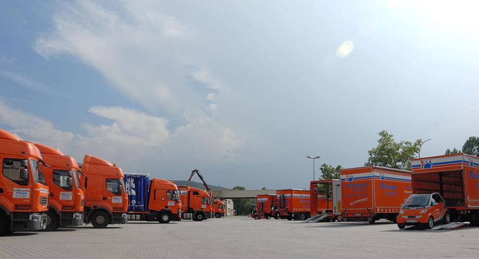 Mans ieht viele LKW für Maschinentransporte nebeneinander stehen. Alle sind orange. Vorne ist auch ein kleiner orangener Smart zu sehen. Oben braut sich bleiern ein Gewitter zusammen.