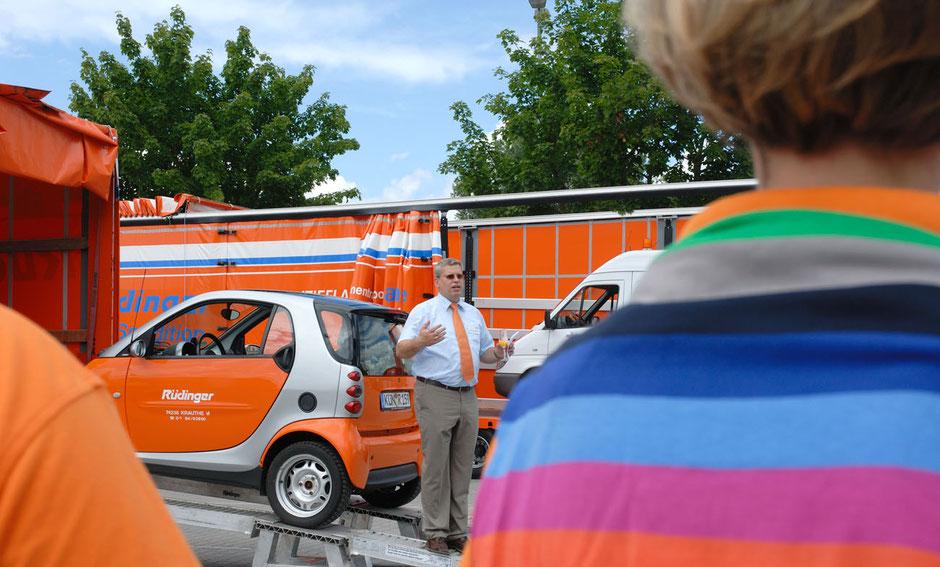 Der Inhaber der Spedition Rüdinger steht hinter dem Smart der Firma Rüdinger in orange, der gerade auf einen Maschinentransporter aufgeladen wird. Auffällig vorne rechts: ein tolles farbiges T-Shirt.