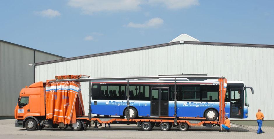 Oben im blauen Himmel mit weißen Wolken steht Bustransport Rüdinger Spedition. Man sieht einen großen blauen Bus in einem noch größeren Maschinentransport LKW. Die Planen sind alle offen.