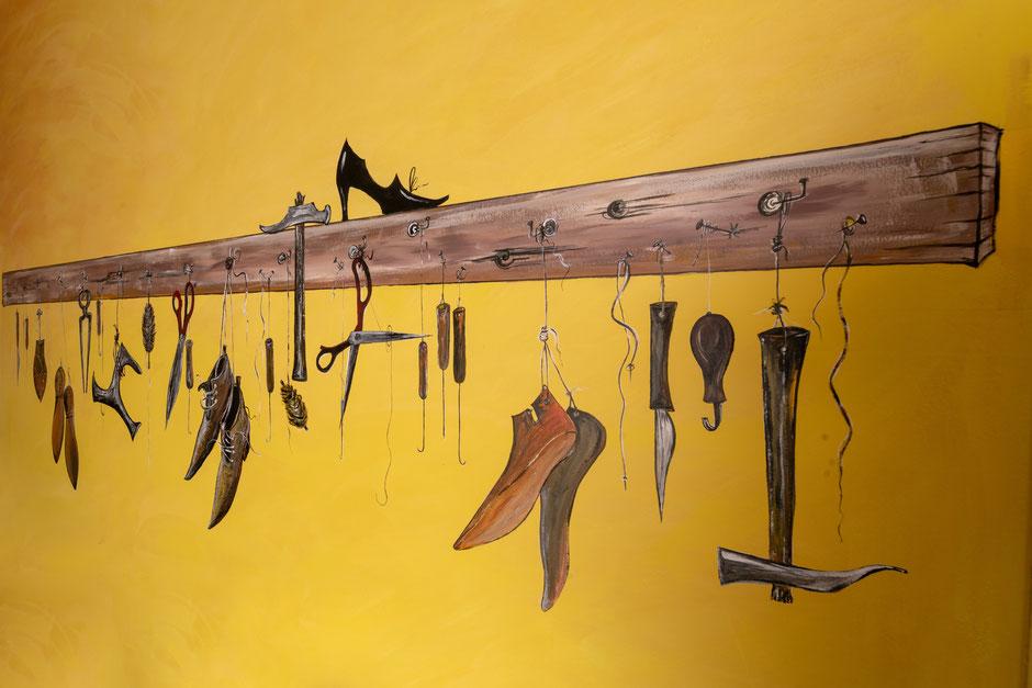 Detaillirte Acrylmalerei auf feingeschliffener Wand.  Das Bild zeigt Werkzeuge des Schusterhandwerks.