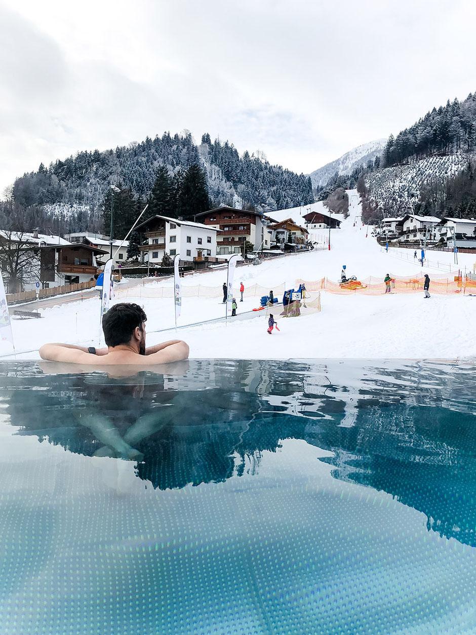 """DaySpa in Tirol:  Hotel Schwarzbrunn in Stans - Open-Air-Pool """"Bergsee"""" mit Blick auf die Tuxer Voralpen und den Burglift Stans"""