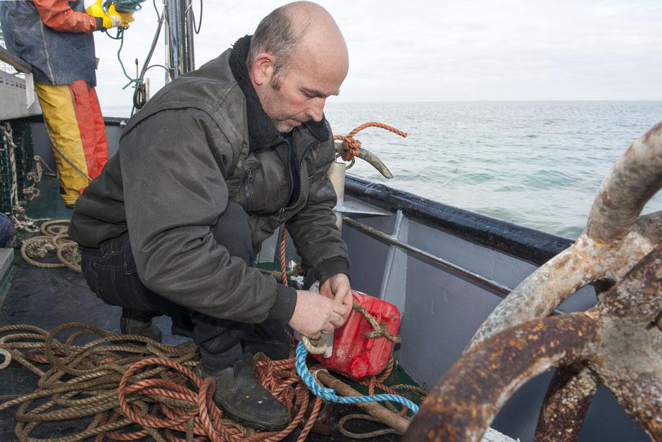 Jan Zoeteweij bevestigt een tonnetje aan de lijn om de plaats van een kreeftenkorf te markeren | © TekstEnPlaat.nl