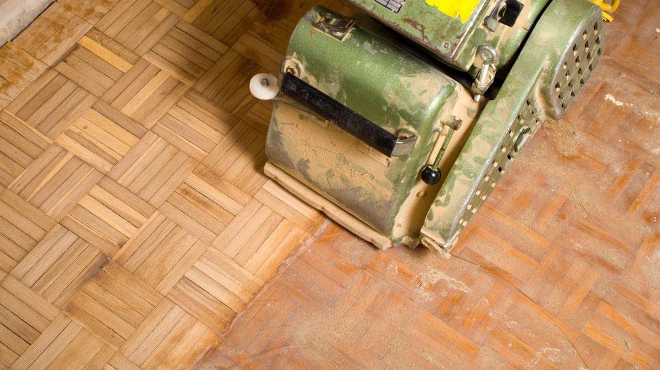 Bild: Walzenschleifmaschine auf Eiche Mosaikparkett; links bereits geschliffen-roh und noch unbehandelt; rechts der Bestandsboden