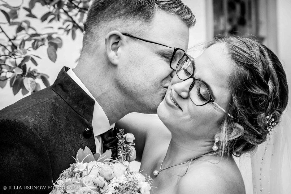 Schwarzweissfoto, Brautpaar post romantisch vor der Kirche in Neuenegg