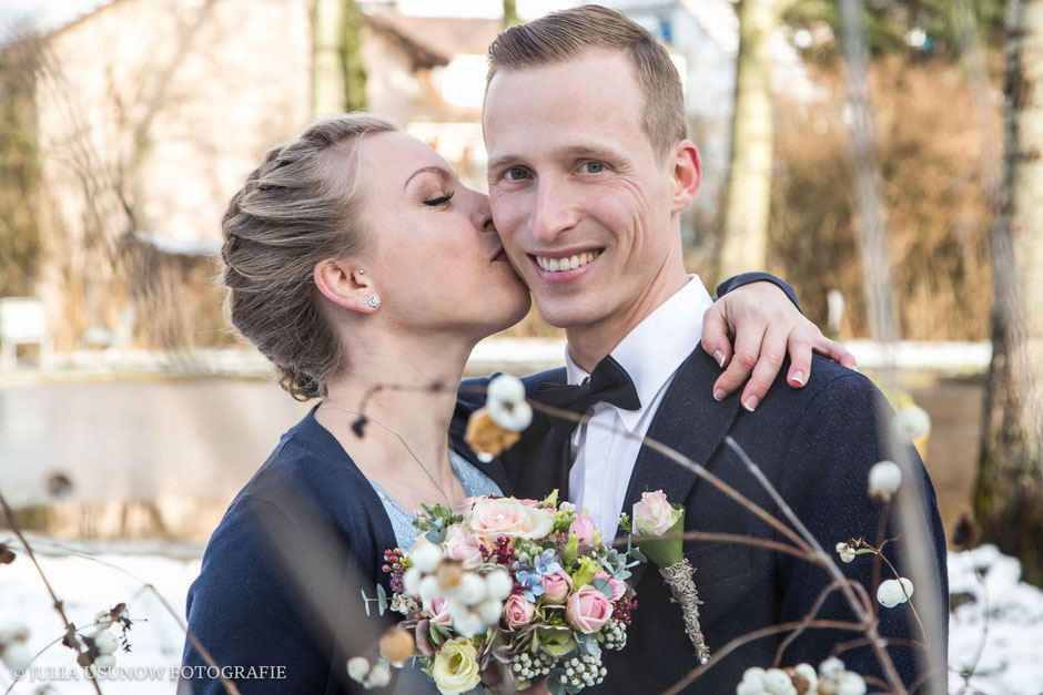 Braut küsst Bräutigam im Winter