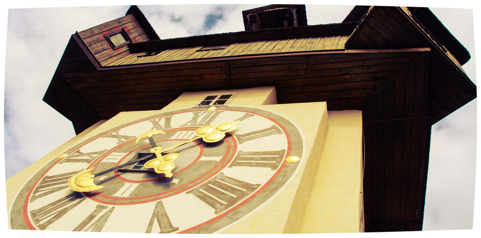 Grazer Uhrturm aus der Froschperspektive (Aufnahme von unten) mit überdimensional erscheinender Uhr und der darüber auskragenden Holzkonstruktion des Dachstuhls - Brandschutzkonzept