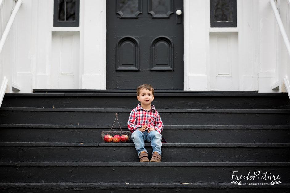 Kinderfoto Bub auf Treppe mit Obstkorb in Jeans und Carohemd