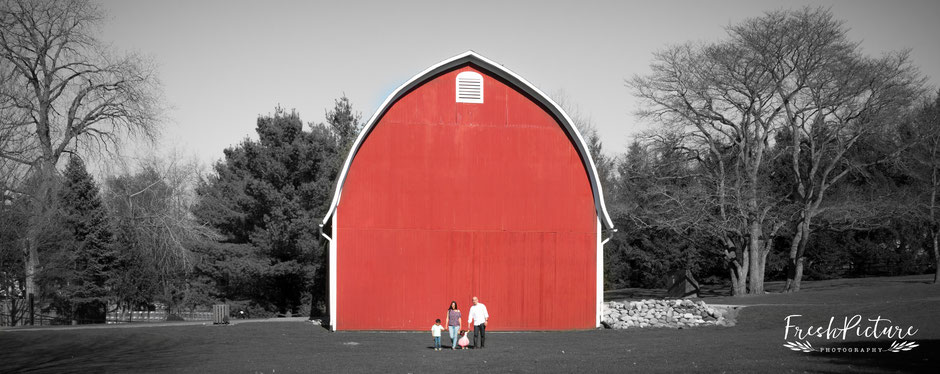 Foto von Familie mit Kindergartenkinder in schwarz/weiss vor roter Farm/Scheune in rustikaler Umgebung mit Natur.