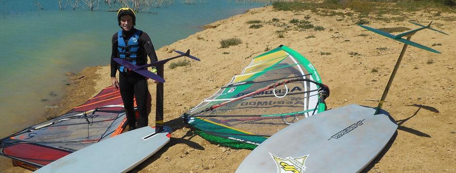 sur la plage au lac de la Ganguise, deux planches à voiles montées avec leur windfoil Aeromod, et Franck Gressier souriant, avec combinaison, gilet de flotaison et casque