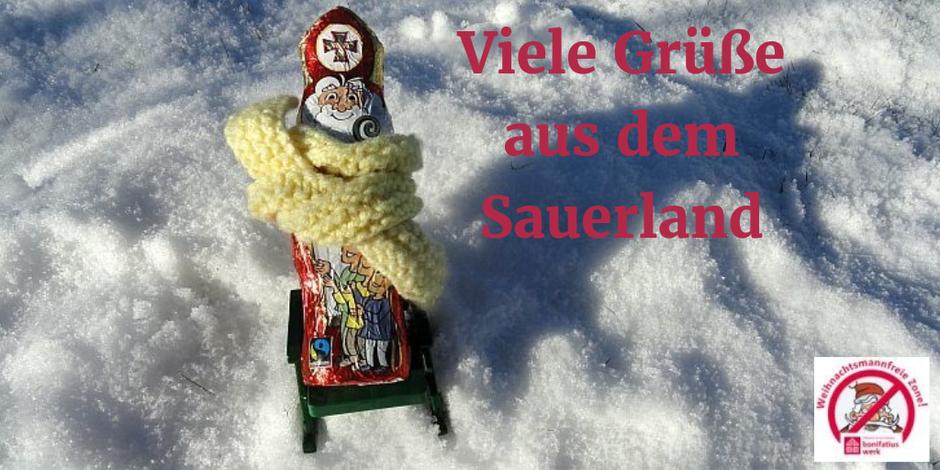 Mit einem dicken gelben Schal sitzt der Nikolaus auf einem Liegestuhl im Schnee.
