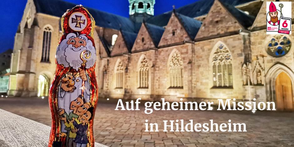 Der Schokonikolaus steht bei Nachtdämmerung vor dem angestrahlten Hildesheimer Dom