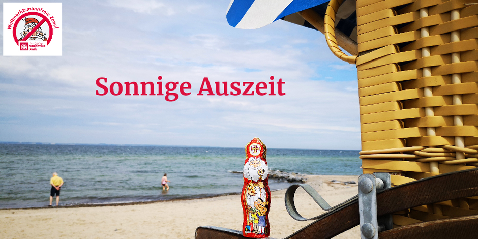 """Der Schokonikolaus steht auf einem """"Arm"""" eines gelben Strandkorbes. Im Hintergrund sieht man den Strand, das Meer und eine Frau und einen Mann, die am Wasser stehen"""