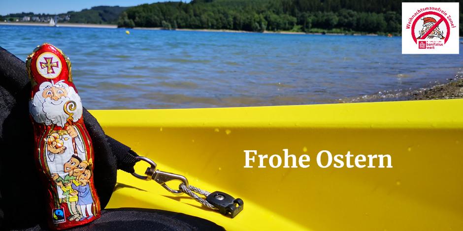 Der Schokonikolaus sitzt in einem Kanu mit schwarzem Sitz und gelber Reling. Im Hintergrund ein See mit angrenzendem Wald.