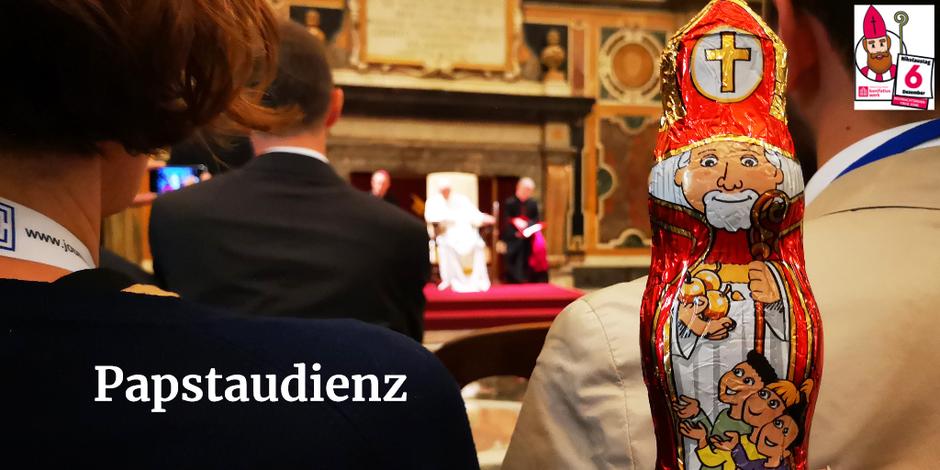 Der Schokonikolaus schaut in die Kamera, hinter ihm sitzen Menschen, mit dem Rücken zu ihm, in der Mitte des Bildes sieht man Papst Franziskus.