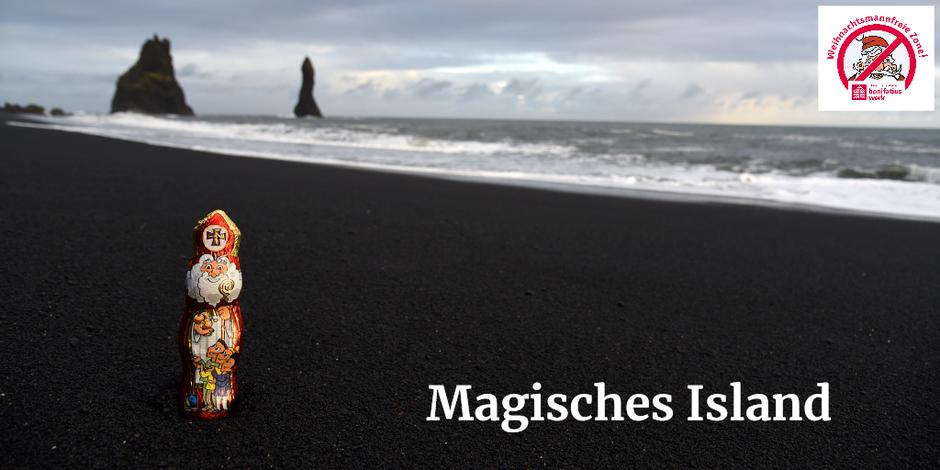 Der Schokonikolaus steht auf einen schwarzen Sandstrand. Im Hintergrund das Meer und zwei hohe Felsen, die aus dem Meer ragen.
