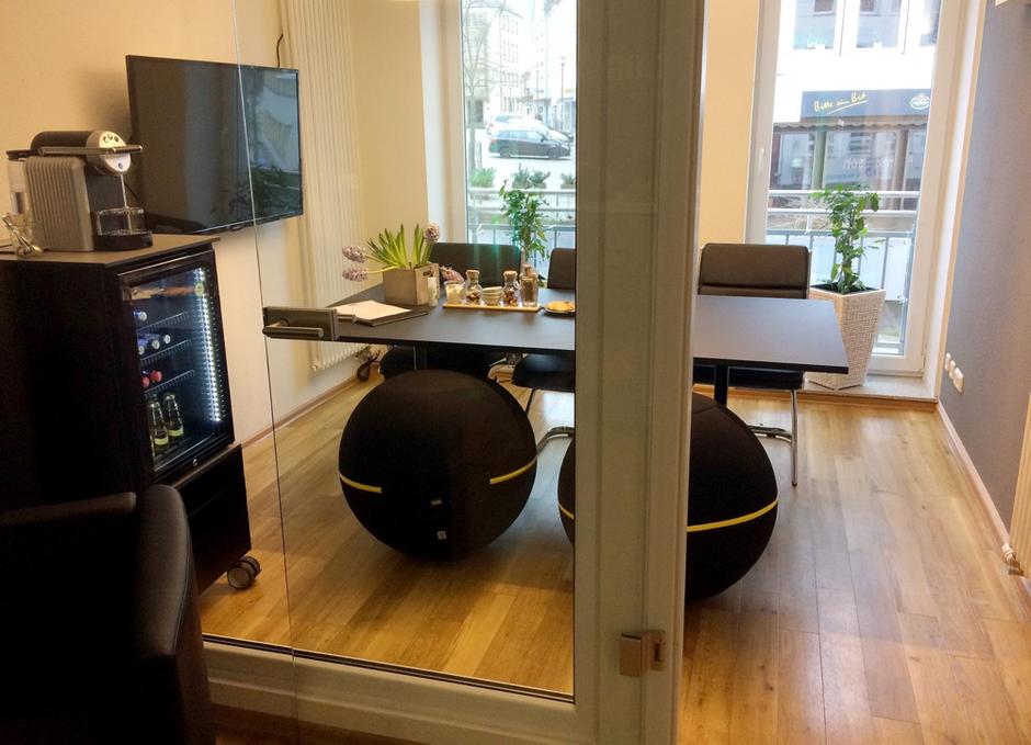 Ansicht eines kleinen Meetingraums von außen fotografiert durch die Glaswand