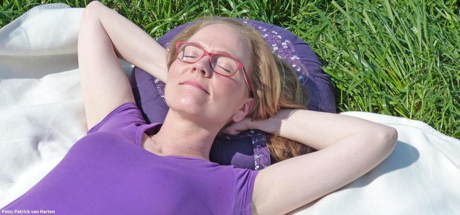 Barbara Dondrup von Routenwechsel liegt auf einer grünen Wiese und genießt ihre Pause.